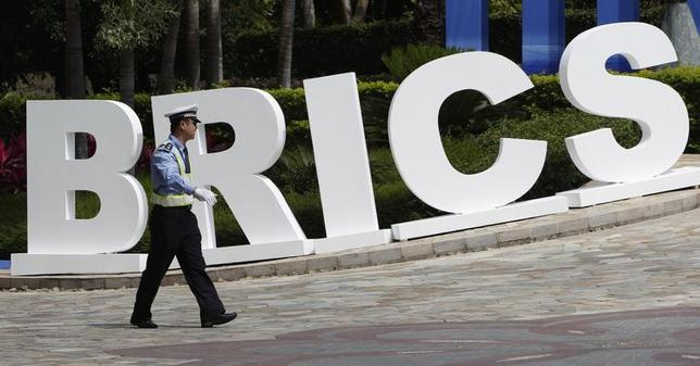 A traffic policeman walks past a signage decoration for BRICS Summit outside the Sheraton Hotel, the venue of BRICS (Brazil, Russia, India, China and South Africa) Summit in Sanya, China's Hainan province, April 13, 2011. REUTERS/Jason Lee