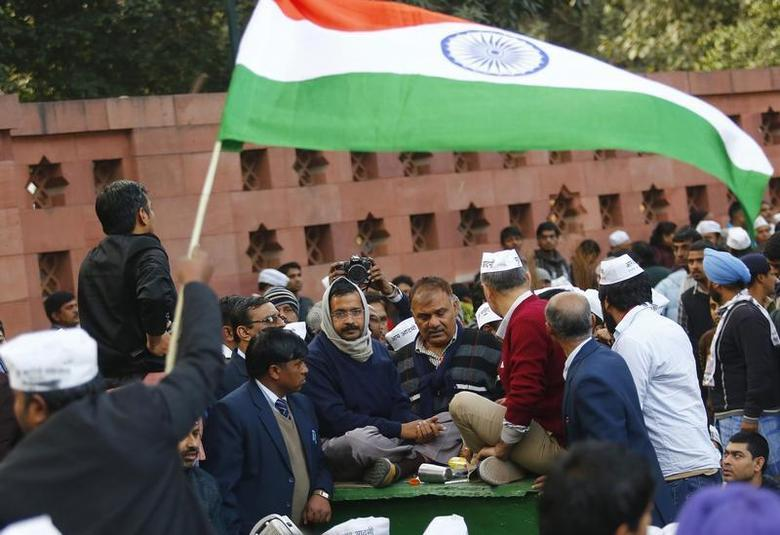 A supporter of Aam Aadmi (Common Man) Party (AAP) flutters India's national flag as Delhi's chief minister Arvind Kejriwal (C) takes part in a protest in New Delhi January 20, 2014. REUTERS/Anindito Mukherjee