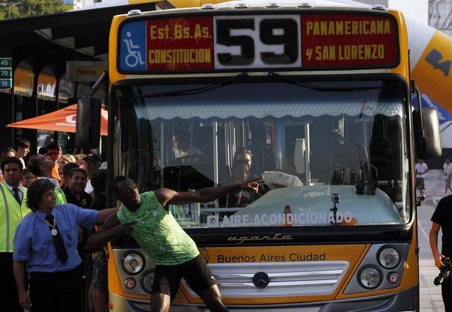 Jamaican sprinter Usain Bolt poses next to the bus driver after competing in a race against a public bus during a demonstration event in Buenos Aires December 14, 2013. REUTERS/Marcos Brindicci
