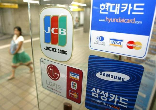 A South Korean woman walks past a shop window bearing stickers of credit card companies in Seoul July 8, 2005. REUTERS/You Sung-Ho/Files