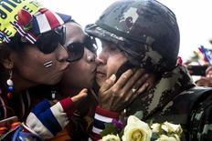Антиправительственные демонстранты целуют солдата тайской армии в Бангкоке 19 января 2014 года. Правительство Таиланда ввело чрезвычайное положение сроком на 60 дней в Бангкоке и прилегающих к нему провинциях, начиная с 22 января, чтобы сдержать протестующих, которые заблокировали отдельные районы столицы. REUTERS/Nir Elias