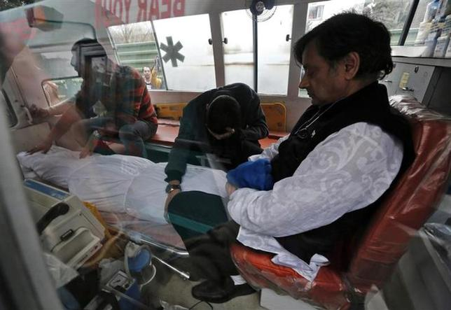 Minister of State for Human Resource Development Shashi Tharoor (R) sits next to the body of his wife Sunanda Puskhar Tharoor inside an ambulance after a post-mortem at a hospital in New Delhi, January 18, 2014. REUTERS/Adnan Abidi