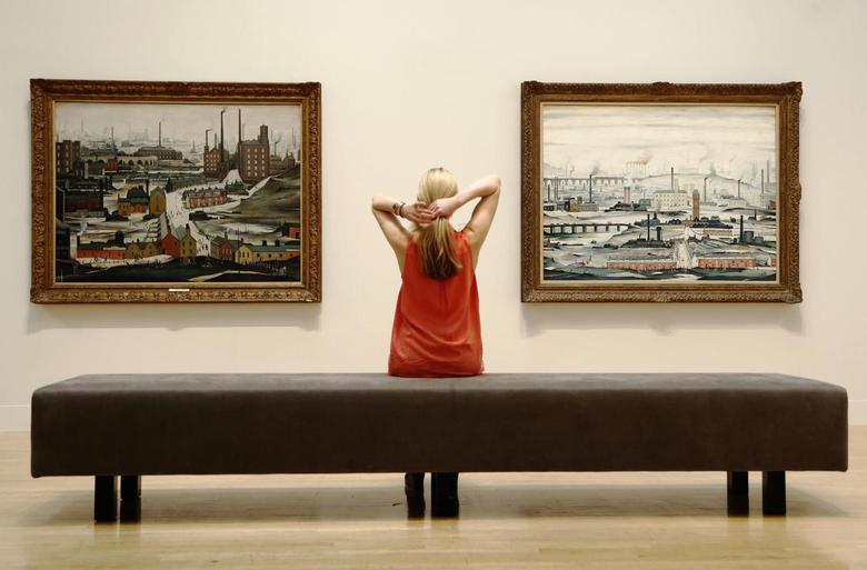 A file photograph shows a Tate employee posing for a photograph with works by British artist L.S.Lowry at Tate Britain in London June 24, 2013. REUTERS/Luke MacGregor/Files