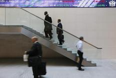 People walk past an electronic information board at the London Stock Exchange in the City of London October 11, 2013. REUTERS/Stefan Wermuth