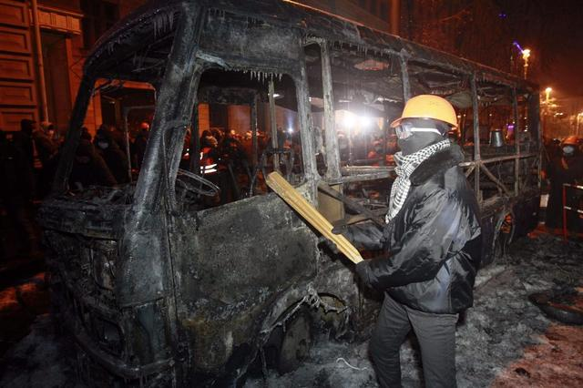 A pro-European protester looks at the wreckage of a vehicle burnt during clashes with Ukranian riot police in Kiev January 20, 2014. REUTERS/Gleb Garanich