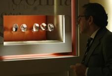 """A visitor looks at watches at the Parmigiani booth during the opening day of the """"Salon International de la Haute Horlogerie"""" at Palexpo in Geneva, January 19, 2009. REUTERS/Denis Balibouse"""