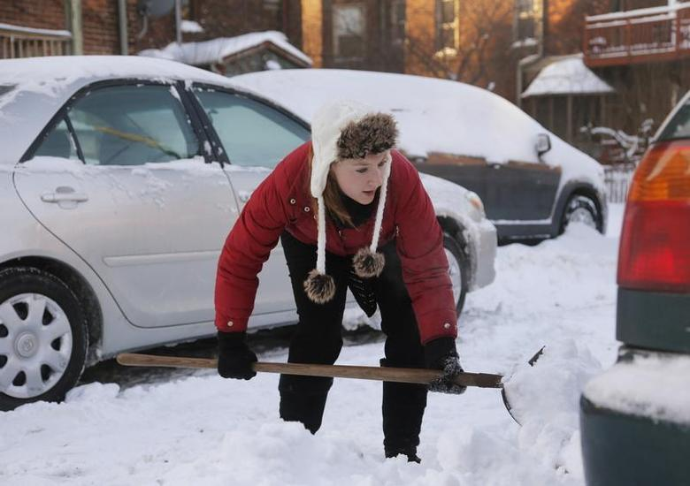 Jessica Corner shovels snow so she can move her vehicle from behind the apartment building she lives in during bitter cold temperatures in Detroit, Michigan January 7, 2014. REUTERS/Rebecca Cook
