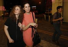 Members of Russian punk rock band Pussy Riot, Nadezhda Tolokonnikova (C) and Maria Alyokhina, leave the inaugural Prudential Eye Awards in Singapore January 18, 2014. REUTERS/Edgar Su
