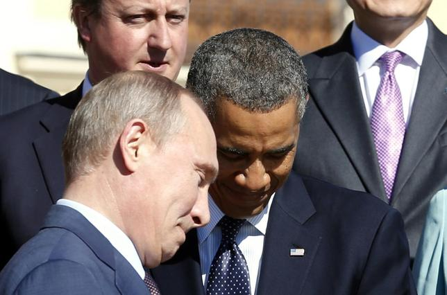 Russian President Vladimir Putin (L) walks past U.S. President Barack Obama (C) during a group photo at the G20 Summit in St. Petersburg September 6, 2013. At top left is British Prime Minister David Cameron. REUTERS/Kevin Lamarque