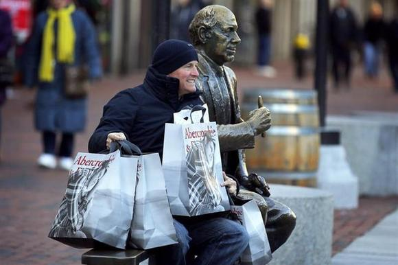 A man poses for a photograph with his shopping bags and a statue of hall of fame Boston Celtics coach Red Auerbach on Black Friday in Boston, Massachusetts November 29, 2013. REUTERS/Brian Snyder