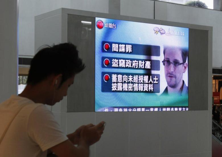 A man checks his mobile phone in front of a monitor broadcasting news on U.S. charges against Edward Snowden, a former contractor at the National Security Agency (NSA), at a shopping mall in Hong Kong June 22, 2013. REUTERS/Bobby Yip