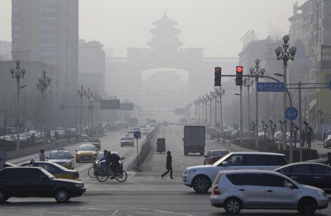 Pedestrians cross the road near the Beijing West Railway Station (background) on a hazy day in Beijing, January 17, 2014. REUTERS/Jason Lee