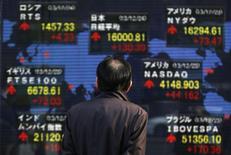 Прохожий смотрит на экран с рыночными котировками у брокерской конторы в Токио 24 декабря 2013 года. Азиатские фондовые рынки выросли в среду за счет действий центробанков Китая и Японии и финансовых отчетов компаний. REUTERS/Yuya Shino