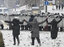 Люди приближаются к шеренге бойцов внутренних войск во время столкновений силовиков и сторонников евроинтеграции в Киеве 22 января 2014 года. Милиция дубинками теснит протестующих на подступах к парламенту и правительству Украины в центре Киева, после того как на утро четвертого дня столкновений стало известно о гибели трех человек. REUTERS/Gleb Garanich