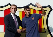 Brazilian soccer player Neymar (R) shakes hands with Barcelona's president Sandor Rosell after signing a five-year contract with FC Barcelona, in front of their offices close to Camp Nou stadium in Barcelona in this June 3, 2013 file photo. REUTERS/Albert Gea