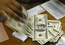 Um cambista com uma pilha de dólares norte-americanos em Jacarta. O fluxo cambial, entrada e saída de moeda estrangeira do país, ficou negativo em 677 milhões de dólares na semana passada, acumulando no mês saídas líquidas de 1,894 bilhão de dólares, informou o Banco Central nesta quarta-feira. 29/08/2013 REUTERS/Beawiharta