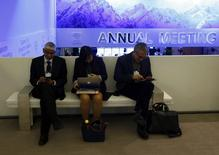 Participants use their smart phones and laptops as they sit on a bench between sessions during the annual meeting of the World Economic Forum (WEF) in Davos January 22, 2014. REUTERS/Denis Balibouse
