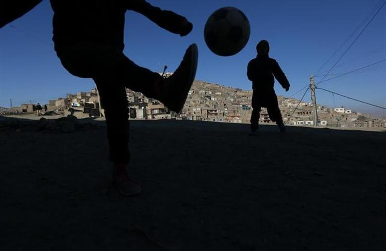 Afghan children play soccer in Kabul January 15, 2014. REUTERS/Omar Sobhani