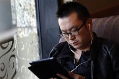 """Un hombre utiliza una tableta iPad en una cafetería en Shanghái, nov 28 2013. Un error humano fue la causa probable de una falla técnica en el """"Gran Cortafuegos"""" chino que irónicamente redirigió a millones de internautas a la página de una empresa con sede en Estados Unidos que ayuda a la gente a evitar la censura en Internet de Pekín, dijeron fuentes a Reuters. REUTERS/Carlos Barria"""