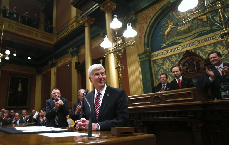 Michigan's Governor Rick Snyder (C) is acknowledged by the Assembly before his annual State of the State address at the State Capitol in Lansing, Michigan January 16, 2014. REUTERS/Rebecca Cook