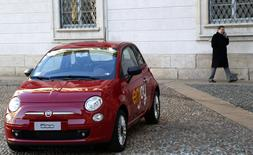 A man walks near a red Fiat 500 car in downtown Milan, December 16, 2013. REUTERS/Stefano Rellandini