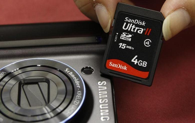 A shopper poses with a SanDisk memory card beside a Samsung camera in Hong Kong September 17, 2008. REUTERS/Bobby Yip