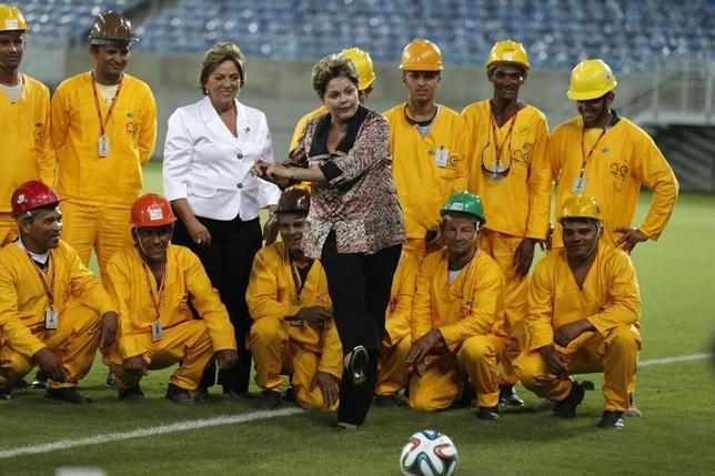 Brazil's President Dilma Rousseff (C) kicks the ball while standing near workers during the opening ceremony of the Arena das Dunas stadium, which will be one of the stadiums hosting the 2014 World Cup soccer matches, in Natal January 22, 2014. REUTERS/Sergio Moraes