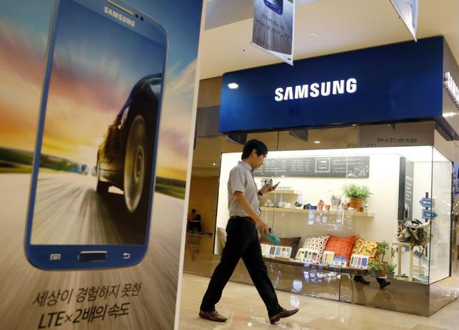 A man using his mobile phone walks past a Samsung Electronics shop in the company's main office building in central Seoul July 23, 2013. REUTERS/Lee Jae-Won