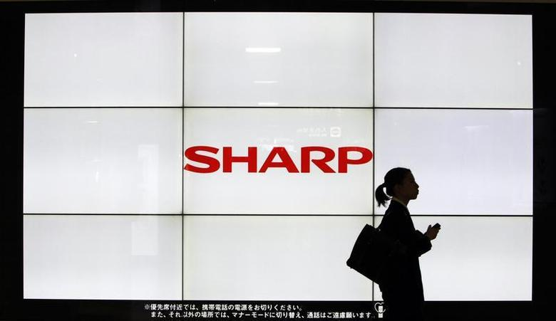 A woman walks past the Sharp Corp's Logo at a train station in Tokyo March 6, 2013. REUTERS/Yuya Shino