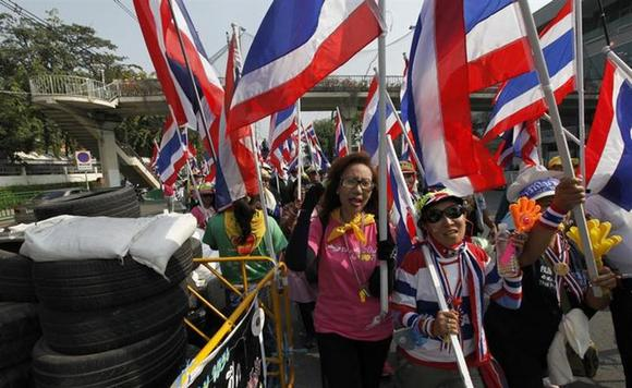 Anti-government protesters with the Thai national flags return to their base at the Government House in central Bangkok, after marching all day January 22, 2014. REUTERS/Paul Barker