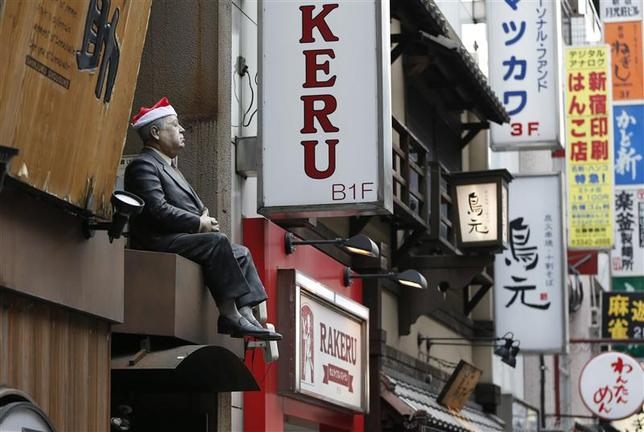 A lifesized doll, adorned with a Santa hat, is seen above the doorway of a restaurant along a street at Tokyo's Shinjuku shopping and business district December 9, 2013. REUTERS/Toru Hanai