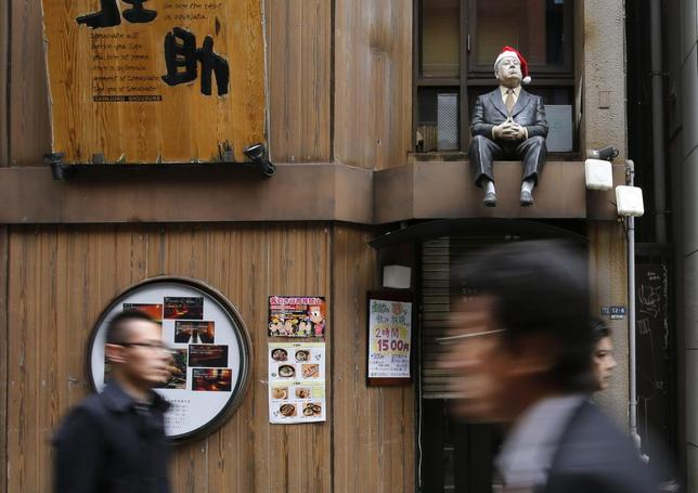 A lifesized doll, adorned with a Santa hat, is seen above the doorway of a restaurant as people walk along a street at Tokyo's Shinjuku shopping and business district December 9, 2013. REUTERS/Toru Hanai