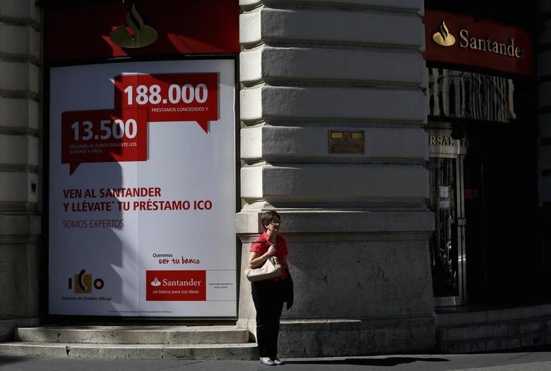 A woman stands outside a Santander bank branch in Madrid October 11, 2013. REUTERS/Juan Medina