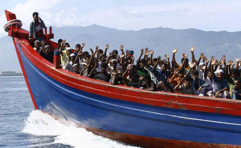Ethnic Rohingya refugees from Myanmar wave as they are transported by a wooden boat to a temporary shelter in Krueng Raya in Aceh Besar April 8, 2013. REUTERS/Junaidi Hanafiah