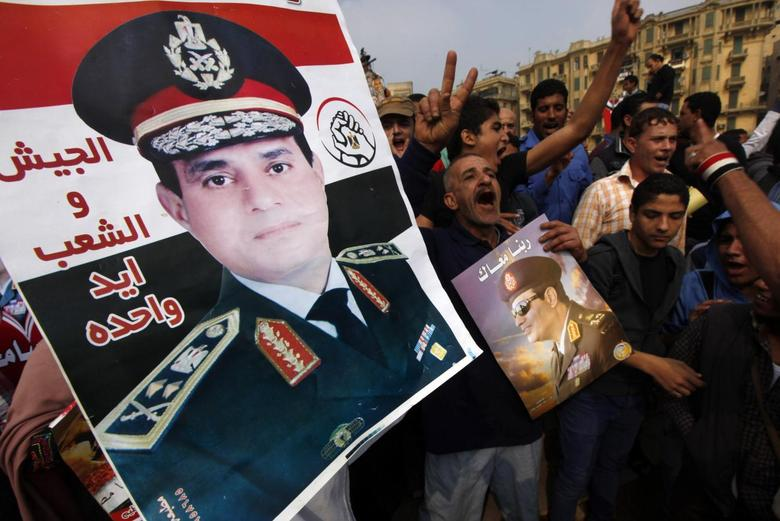 Supporters of Egypt's army chief General Abdel Fattah al-Sisi hold up a poster of Sisi at Tahrir square in downtown Cairo, November 19, 2013. REUTERS/Mohamed Abd El Ghany
