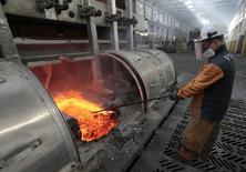 Рабочий у печи на Красноярском алюминиевом заводе 14 августа 2012 года. Промпроизводство РФ выросло в декабре на 0,8 процента в годовом выражении по сравнению с падением на 1,0 процент в ноябре и ростом на 1,4 процента в декабре 2012 года, сообщил Росстат. REUTERS/Ilya Naymushin
