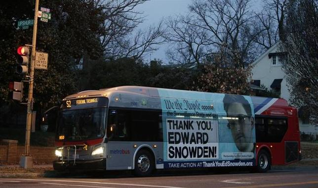 A Washington Metro bus is seen with an Edward Snowden sign on its side panel December 20, 2013. REUTERS/Gary Cameron/Files