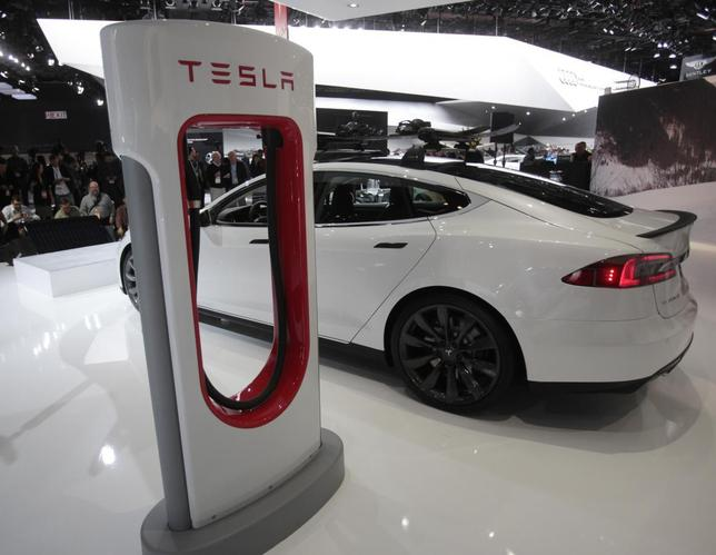 A Tesla S electric car and a charging station are displayed during the press preview day of the North American International Auto Show in Detroit, Michigan January 14, 2014. REUTERS/Rebecca Cook