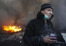"""Протестующий пьет из кружки на фоне горящих автопокрышек на месте столкновений с милицией в центре Киева 23 января 2014 года. Президент Украины Виктор Янукович, которому политические противники на улицах столицы выставили ультиматум, обещая вечером в четверг атаковать силовиков, предложил обсудить кризис на экстренном заседании парламента на следующей неделе и начал новый раунд переговоров с лидерами """"евромайдана"""". REUTERS/Vasily Fedosenko"""