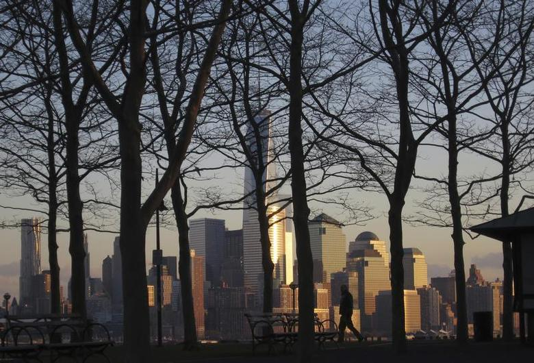 A man walks in a park at sunset across from New York's Lower Manhattan along the Hudson River in Hoboken, New Jersey, November 29, 2013. REUTERS/Gary Hershorn