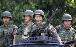 Киргизские военные на грузовике в Оше 29 июня 2010 года. Погранслужба Киргизии сообщила об уничтожении 11 неизвестных вооружённых людей близ границы с населённом мусульманами Синьцзян-Уйгурским автономным районом Китая, где столкновения протестующих с полицией в декабре унесли 14 жизней. REUTERS/Shamil Zhumatov