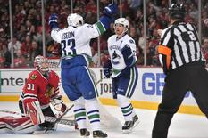 Dec 20, 2013; Chicago, IL, USA; Vancouver Canucks left wing Daniel Sedin (22) celebrates with center Henrik Sedin (33) after scoring a goal against Chicago Blackhawks goalie Antti Raanta (31) during the third period at the United Center. Rob Grabowski-USA TODAY Sports