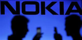 Las sombras de unas personas reflejadas detrás de un logo de Nokia en Zenica, Bosnia-Herzegovina, ene 23 2014. Nokia reportó una caída interanual de un 22 por ciento en las ventas en su unidad de equipos de redes, el negocio principal con el que se quedará tras la venta de su negocio de teléfonos a Microsoft por 5.400 millones de euros (7.400 millones de dólares). REUTERS/Dado Ruvic