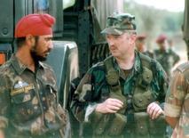 Американский военный разговаривает с солдатом-сикхом на совместных учениях в индийской Агре 16 мая 2002 года. Пентагон решил дать военным больше свободы в ношении религиозных атрибутов, таких как тюрбаны и ермолки, в сочетании с военной формой, хотя правозащитники назвали послабления половинчатыми. REUTERS/Str