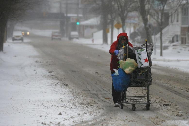 A man pushes a cart up the road while scavenging for bottles and cans during a winter nor'easter snowstorm in Lynn, Massachusetts January 2, 2014. REUTERS/Brian Snyder