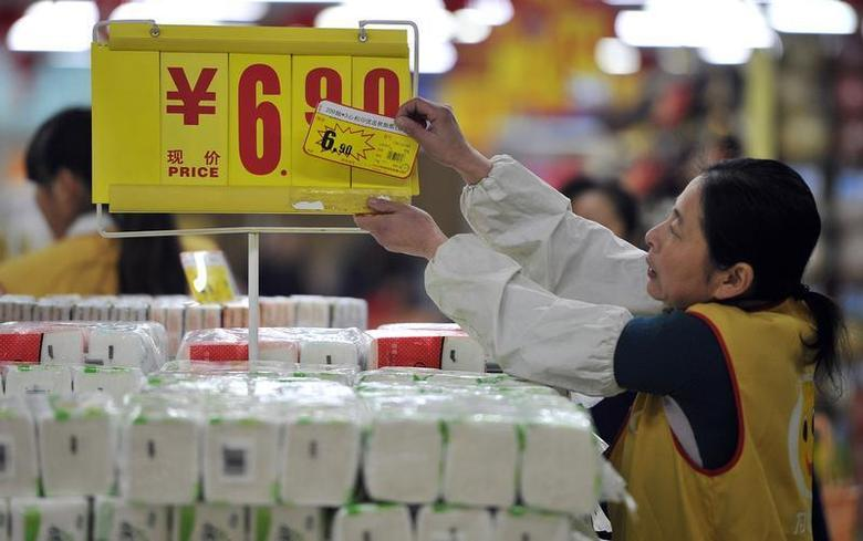 An employee adjusts a price tag of tissues at a supermarket in Hefei, Anhui province January 9, 2014. REUTERS/Stringer