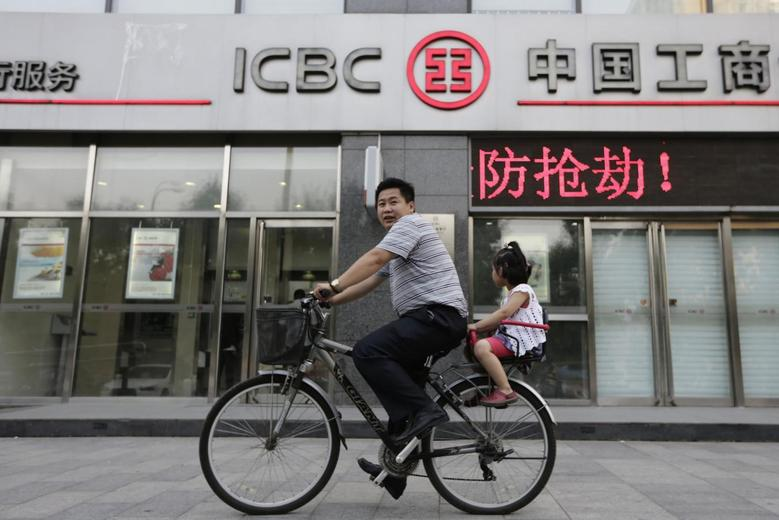 A man and his daughter ride a bicycle past a branch of the Industrial and Commercial Bank of China Ltd (ICBC) in Beijing June 26, 2013. REUTERS/Jason Lee