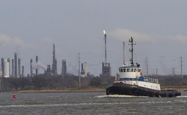 A tug boat navigates the Houston ship channel with a flare from an oil refinery and storage facility in the background south of downtown Houston January 30, 2012. REUTERS/Richard Carson