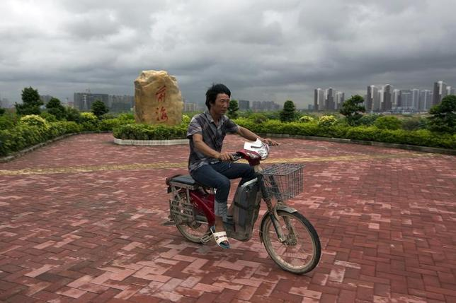 A man rides past a landmark consisting of a rock with the word ''Qianhai'' on it, at the Qianhai special economic zone in Shenzhen August 16, 2013. REUTERS/Tyrone Siu