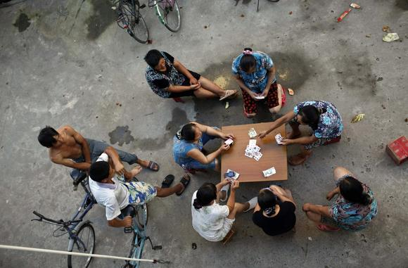 Migrant construction workers gamble with cards after a shift at a construction site in Shanghai August 12, 2013. REUTERS/Aly Song